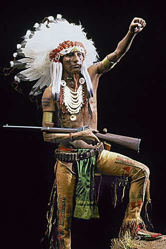 Portrait length color image of Crow Warrior aka.  , by George Stuart.